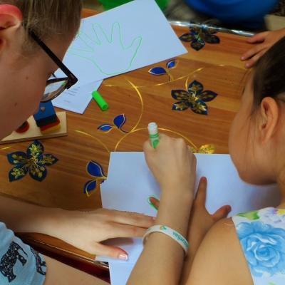 Projects Abroad vrijwilliger werkt met kinderen in Mongolie en helpt een kind met tekenvaardigheden tijdens een educatieve activiteit.